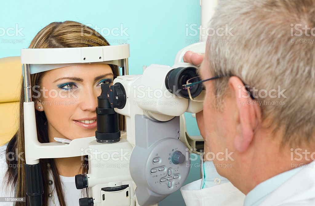 Optometrist Eye Exam Tonometer Optometrist examines the eyes of a young woman patient with a tonometer. 55-59 Years Stock Photo