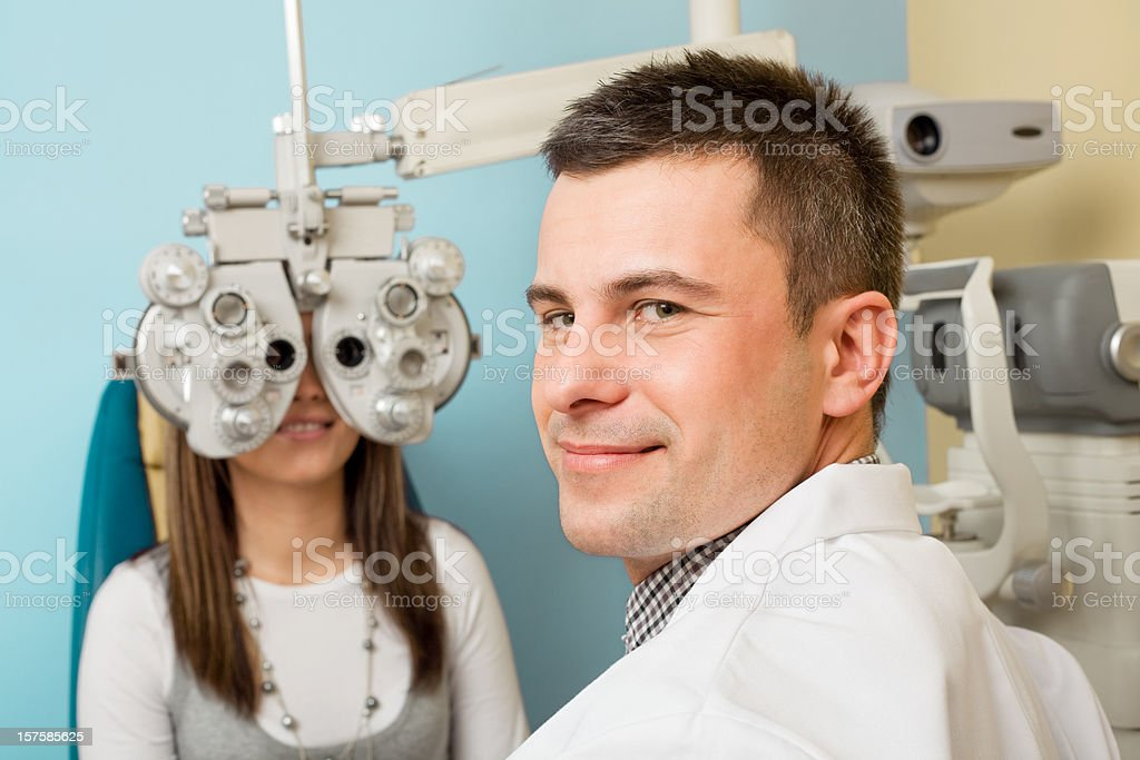 Optometrist Eye Exam Tonometer Optometrist looks at camera while examining the eyes of a young woman patient with a tonometer. 30-34 Years Stock Photo