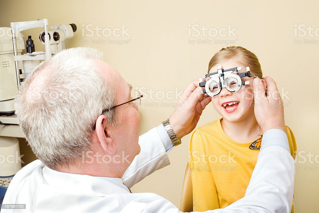 Optometrist Eye Exam Trial Frames Optometrist examines the eyes of a little girl patient with trial frames. 55-59 Years Stock Photo