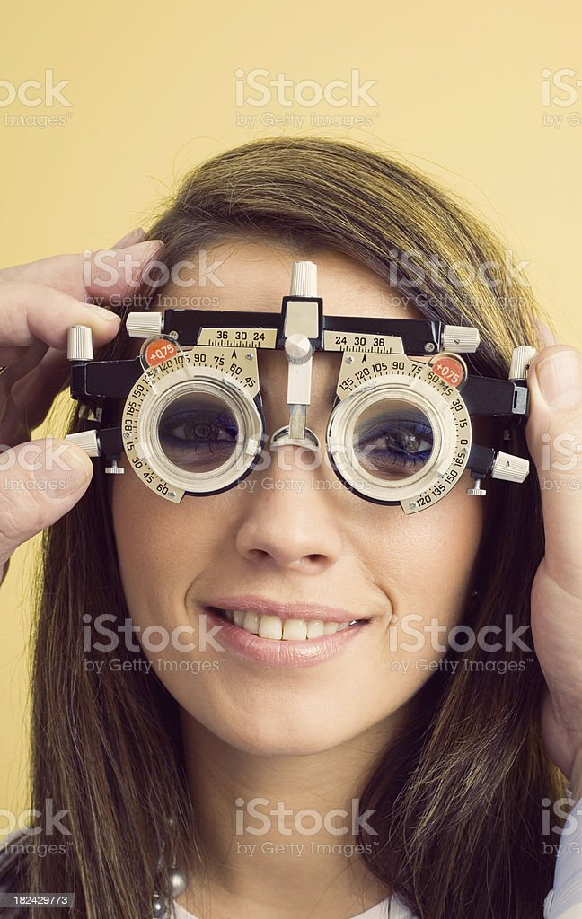 Optometrist Eye Exam Trial Frames Optometrist examines the eyes of a young woman patient with trial frames. Male hands adjusting dial on the trial frames. 25-29 Years Stock Photo