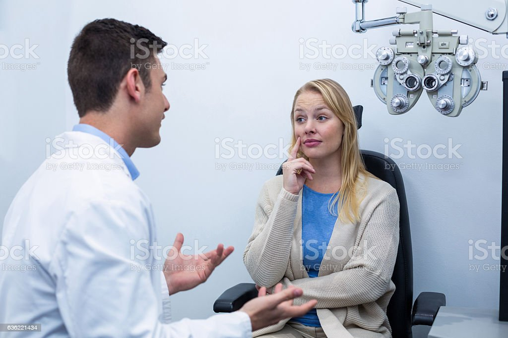 Optometrist interacting with female patient stock photo