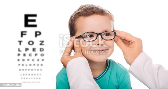 Little boy testing new eyeglasses, optician is adjusting new frame glasses on child's face.