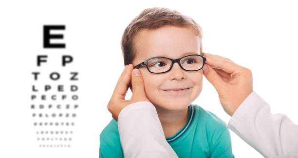 optometrist is putting new glasses on little boy face - optometrist stock pictures, royalty-free photos & images