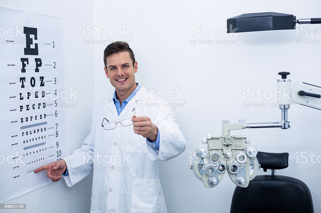 Optometrist pointing at eye chart stock photo