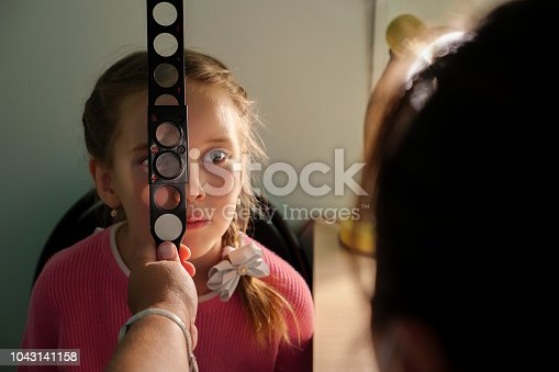 istock optometry concept - medical doctor with magnifier examining little girl 1043141158