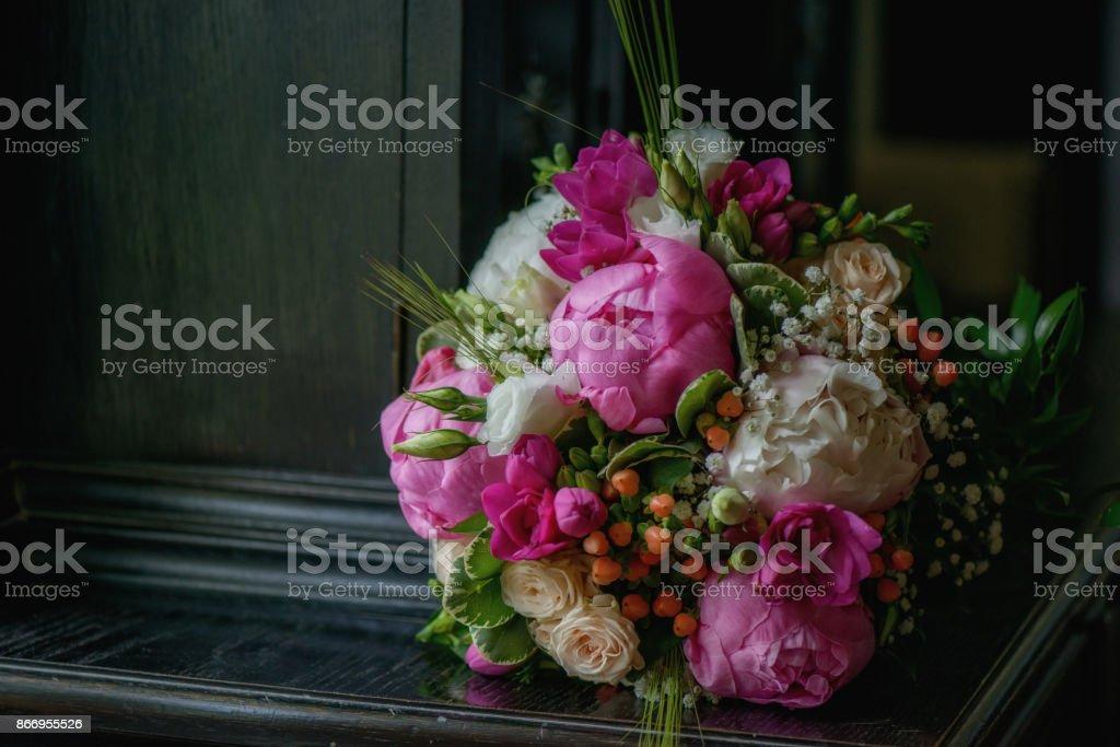 Peonías de color de rosa caliente con opulencia exuberante ramo de novia y las fresias, rosas marfil, flores silvestres y bayas colocadas en un gabinete oscuro vintage - foto de stock