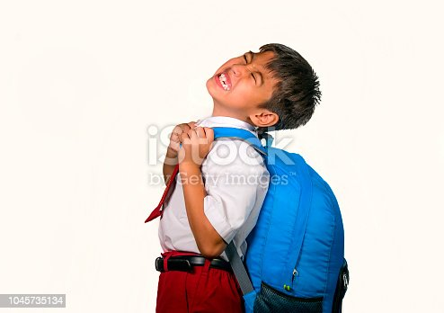 istock 7 or 8 years old sweet kid in uniform carrying bag full of books feeling upset and complaining about the weight of the backpack in lazy schoolboy unhappy about going back to school 1045735134