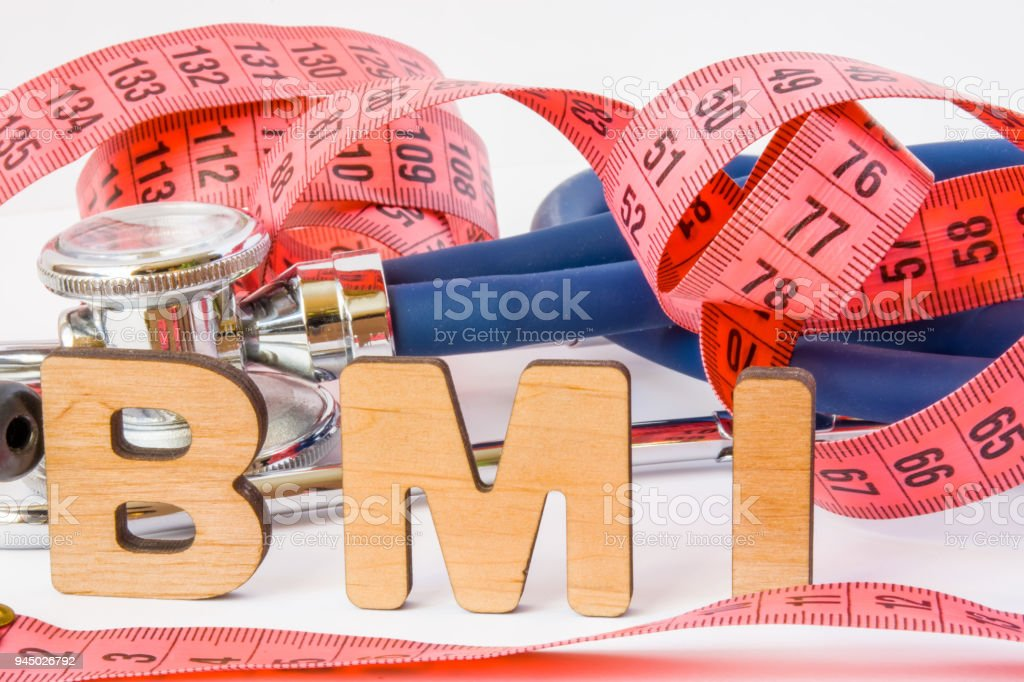 BMI or body mass index abbreviation or acronym photo concept in medical diagnostics or nutrition, diet. Word BMI is on background of tape to measure the circumference of body and medical stethoscope stock photo