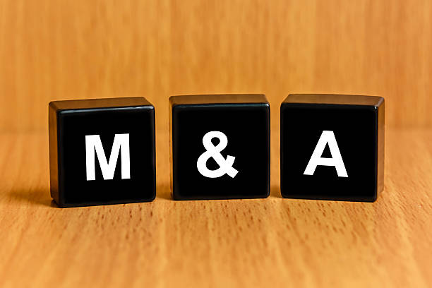 M&A or Merger and Acquisition text on block stock photo