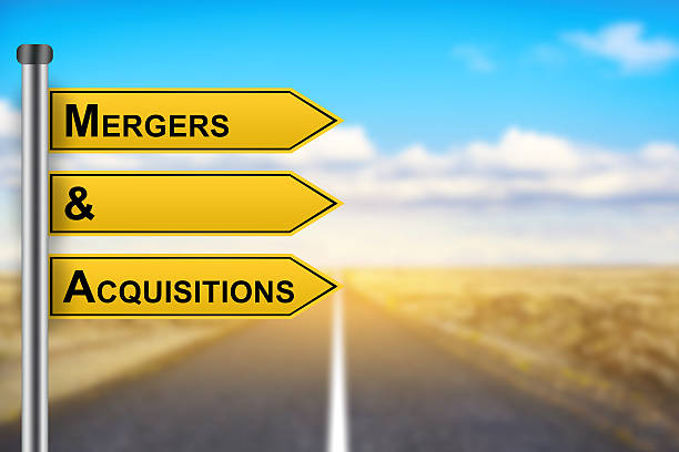M&A or Mergers and Acquisitions words on yellow road sign stock photo