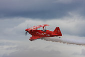 Hillsboro, United States- August 29, 2009: This image shows a red airplane advertising Oracle in mid air, performing aerobatic maneuvers at the Oregon International airshow.