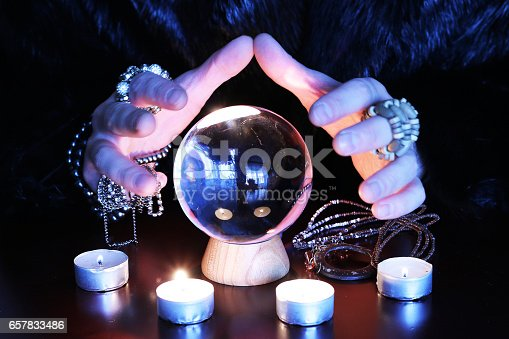 istock Oracle telling future gwith glass orb on a table 657833486