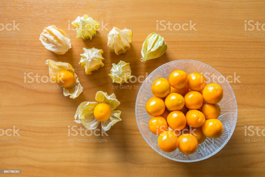 orage gooseberries in glass bowl and some with shell on wood table, delicious fruit high in vitamins stock photo
