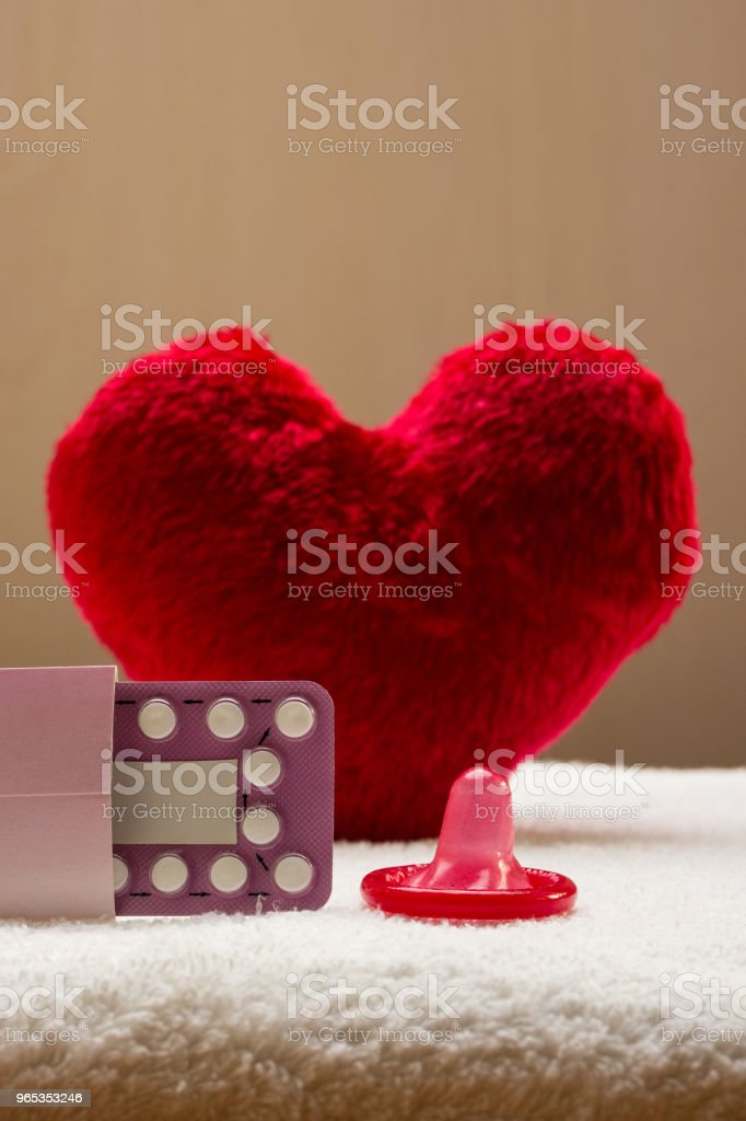 Oral contraceptive pills condom on red heart royalty-free stock photo