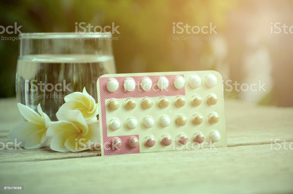 Oral contraceptive pills education wth triphasic pills regimen on natural green background. stock photo