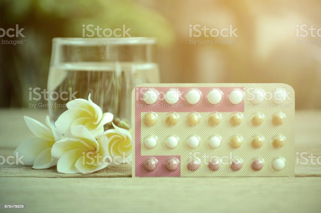 Anticonceptivos orales pastillas educación wth trifásicas píldoras régimen sobre fondo verde natural. - foto de stock
