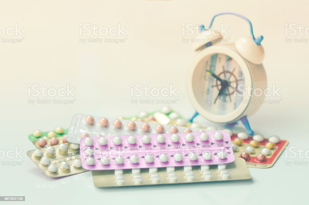 Oral contraceptive pills with alarm clock background in time reminder for taking pills. stock photo