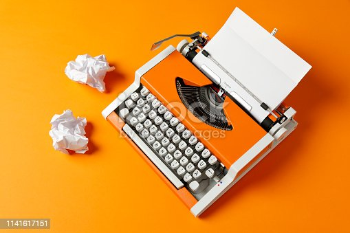 70s typewriter with crumpled paper balls on orange photo carton