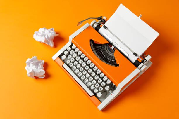 Orange 70s Typewriter mit leerer Seite – Foto
