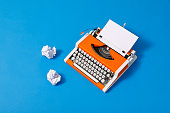 70s typewriter with crumpled paper balls on blue photo carton