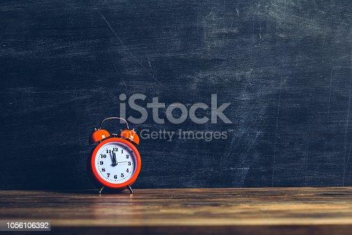 istock Orange alarm clock on a wood shelf in front of empty blackboard 1056106392