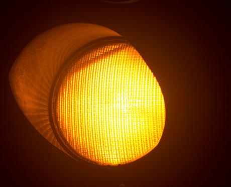 Orange amber traffic light photo at night on black background.
