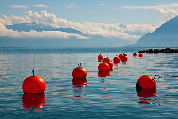 Orange anchor buoys Orange anchor buoys on a surface of quiet lake in mountains buoy stock pictures, royalty-free photos & images