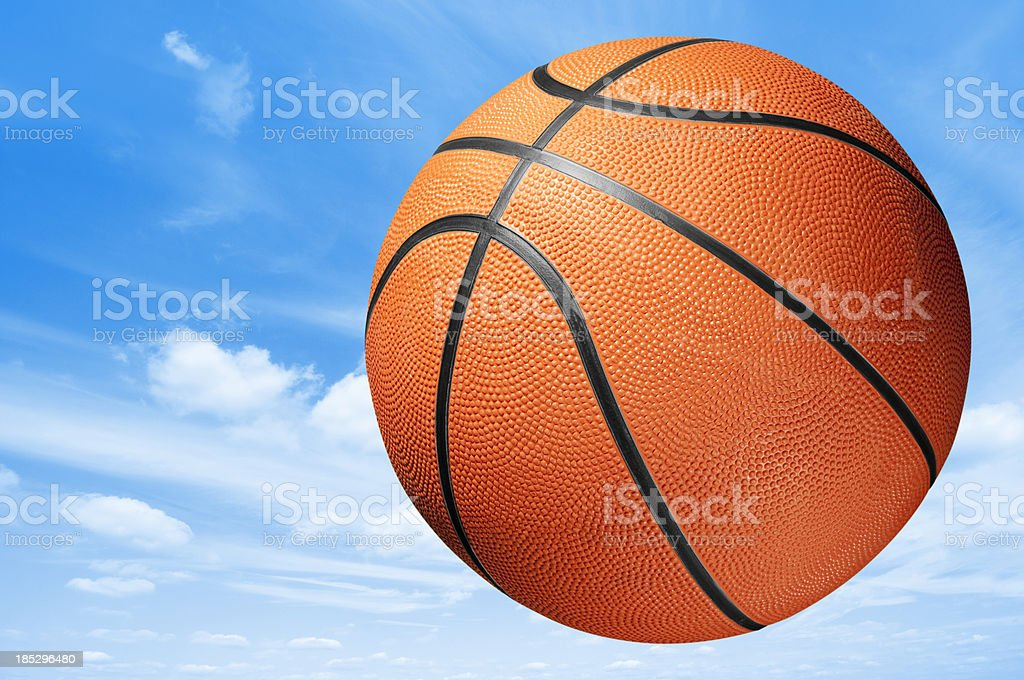 Orange and black basketball midair in blue sky royalty-free stock photo