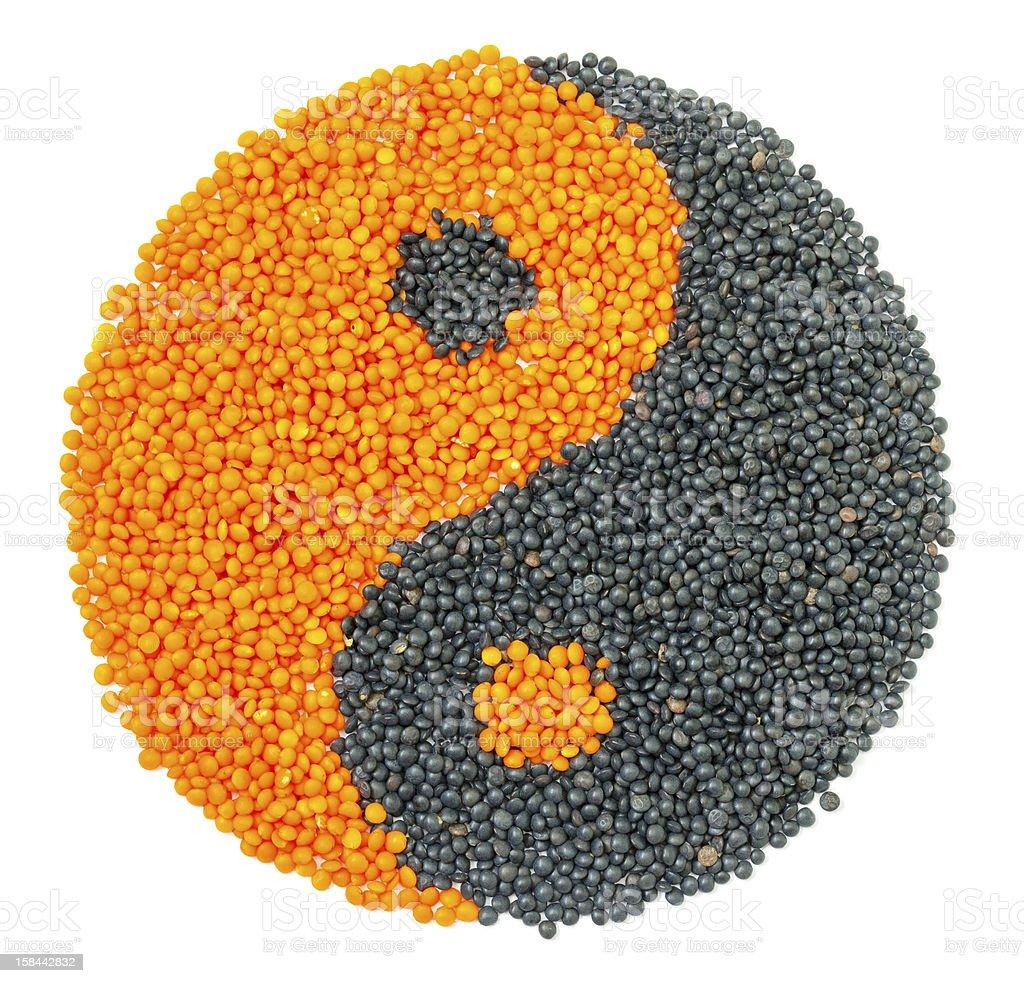 Orange and Black Lentil forming a yin yang symbol royalty-free stock photo