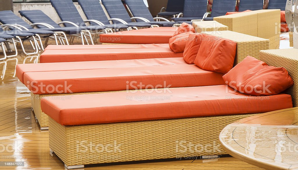 Orange and Blue Chaise Lounges on a Wet Deck royalty-free stock photo