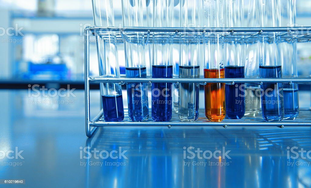orange and blue chemical solution in test tubes in science lab stock photo