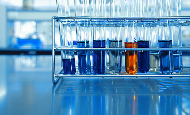 orange and blue chemical solution in test tubes in science lab - foto de stock