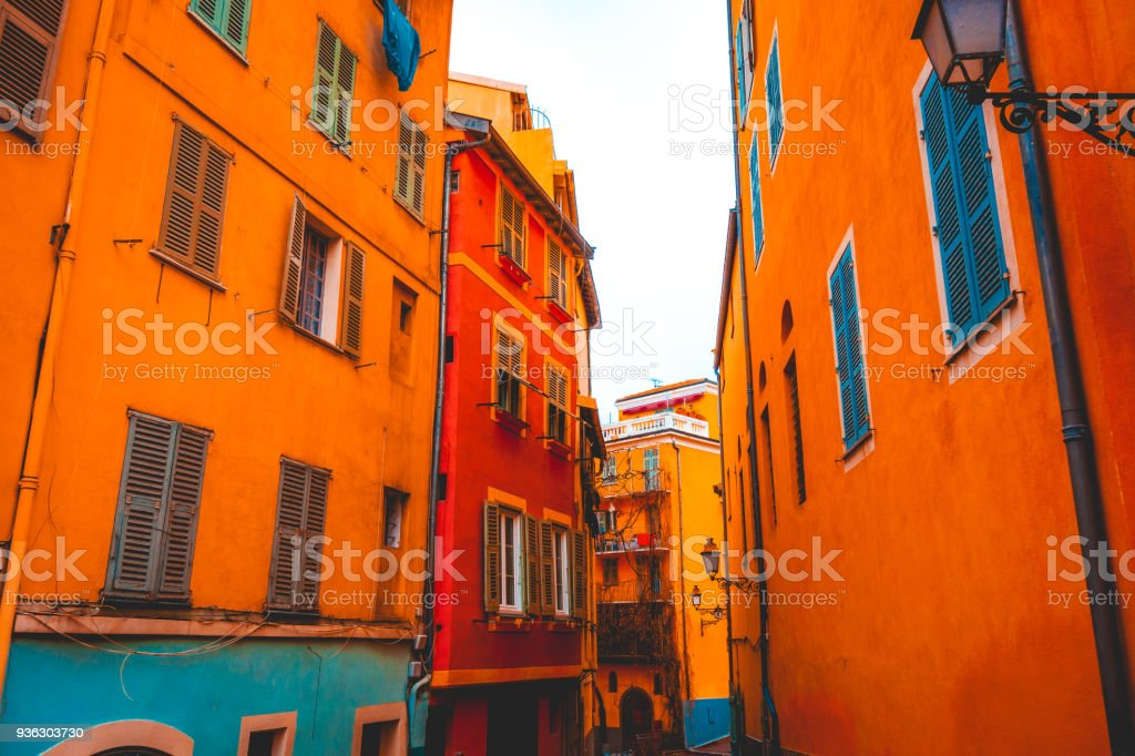 orange and blue facaded houses in a lone alley stock photo