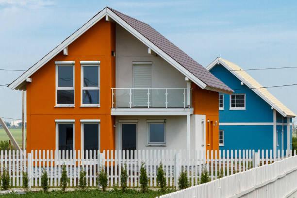 Orange und blau neue Häuser hinter einem weißen Zaun in einer ländlichen Gegend – Foto