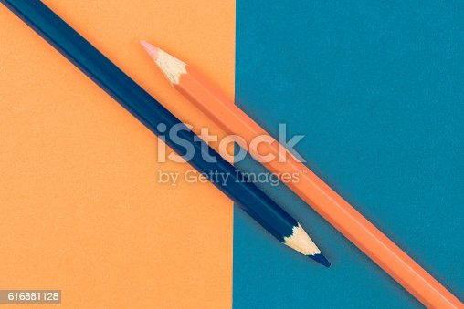 istock Orange and Dark Blue coloured pencils and paper 616881128