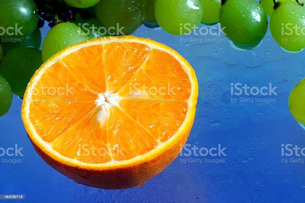 Laranja e uvas em Fundo azul de bebidas - foto de acervo