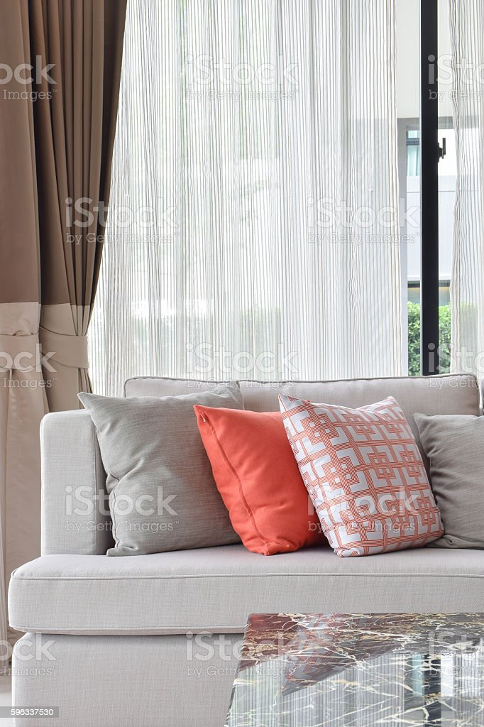Orange and gray pillows setting on sofa in living room Lizenzfreies stock-foto