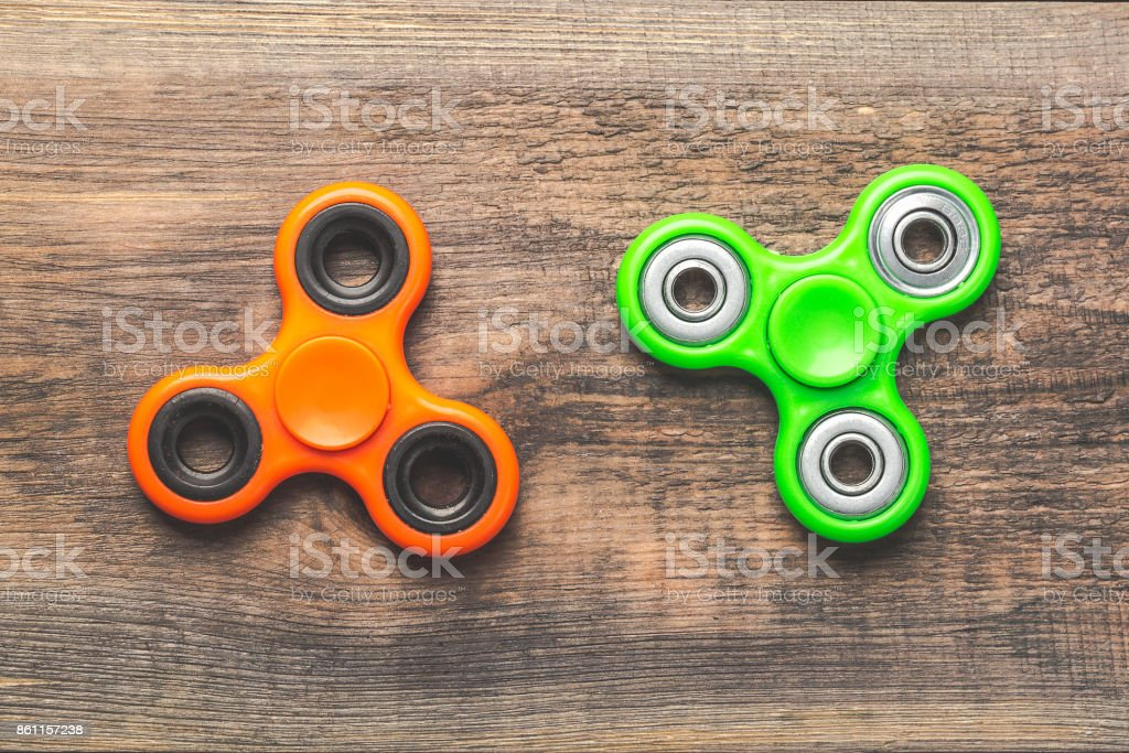 Orange and green fidget spinners close up on each other, stress relieving toys on wooden background. stock photo