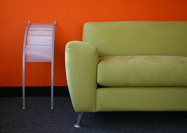 Orange and green Modern green couch in an orange room. Shot with only available window light. magazine rack stock pictures, royalty-free photos & images