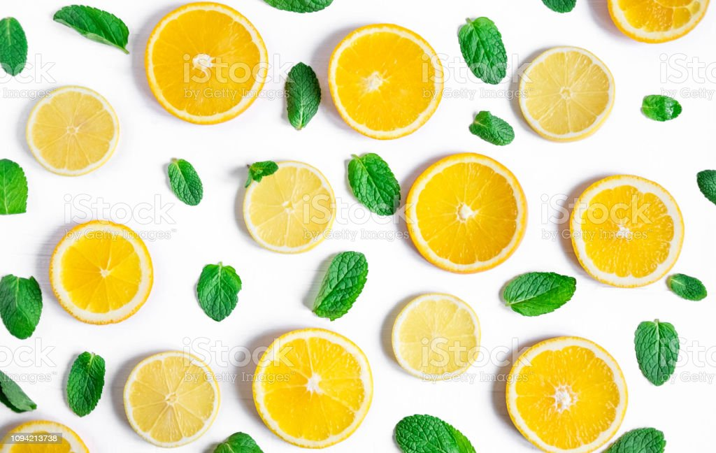 Orange and lemon slices with mint on a white background. Background...
