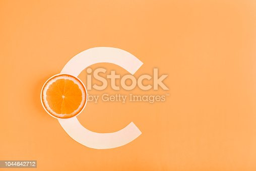 istock Orange and letter C on a yellow background. The concept of Vitamin C. Autumn protection against colds, antioxidant 1044642712