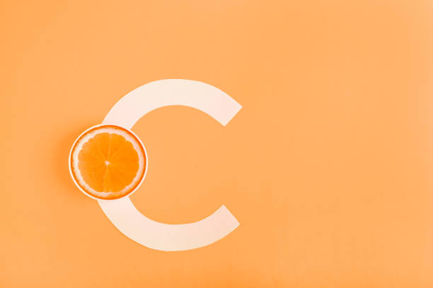 orange and letter c on a yellow background. the concept of vitamin c. autumn protection against colds, antioxidant - deficient stock pictures, royalty-free photos & images
