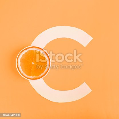 istock Orange and letter C on a yellow background. The concept of Vitamin C. Autumn protection against colds, antioxidant 1044642960