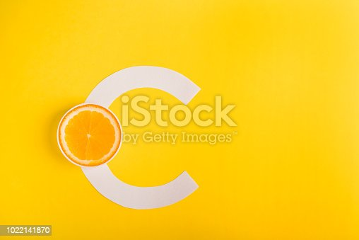 istock Orange and letter C on a yellow background. The concept of Vitamin S. Autumn protection against colds, antioxidant 1022141870