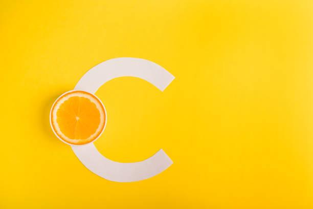 oranje en letter c op een gele achtergrond. het begrip vitamine s. herfst bescherming tegen verkoudheid, antioxidant - vitamine c stockfoto's en -beelden