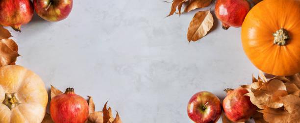Orange und Pfirsich Kürbisse reifen Bio rote glänzende Äpfel Granatäpfel Kastanien trockenen goldenen Herbstblätter auf grauem MarmorStein Hintergrund. Thanksgiving Herbst Ernte Fülle. Langer Banner-Kopierraum – Foto