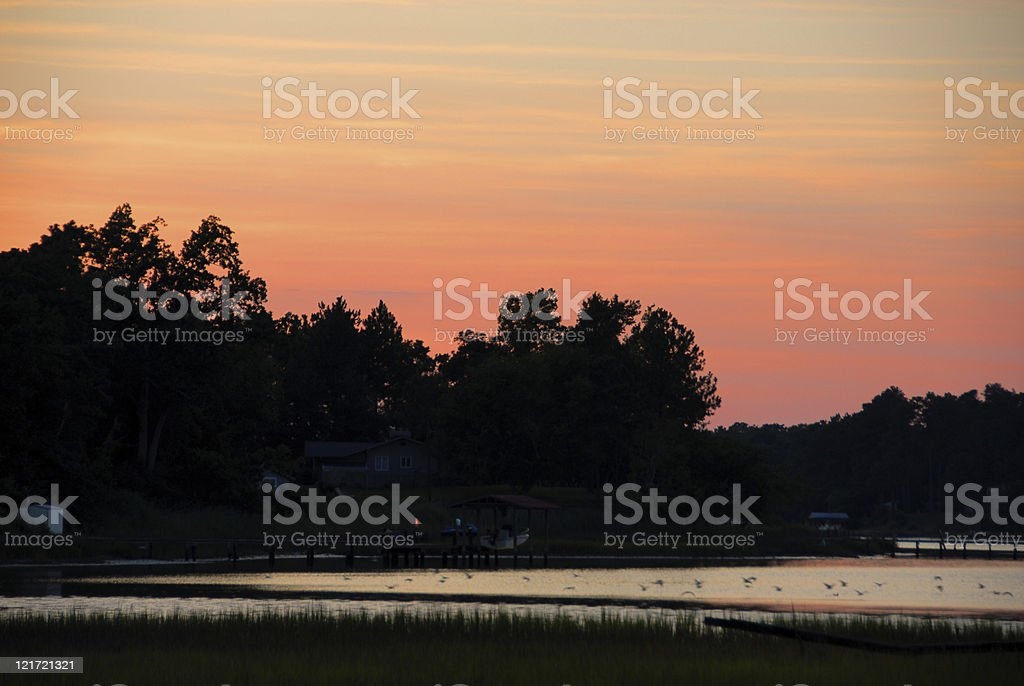 Orange and pink sky during sunset by the river stock photo