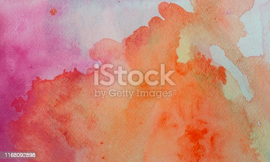 istock Orange and Pink watercolor background on a white paper 1168092898