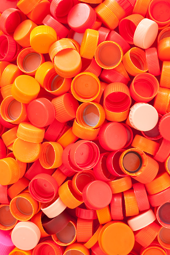 Lots of plastic bottle caps in shades of red