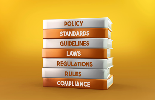 Orange and white Compliance books stand on an orange background. Horizontal composition with copy space. Reading and learning concept.